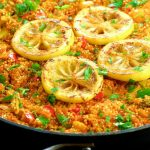 Side view of a paella pan filled with quinoa paella and topped with lemon slices