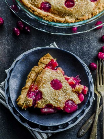 A slice of cranberry pear pie on a black desset plate, over a white and gray stripped cloth napkin. In the background the whole pie on a clear pie dish with a few scatted fresh cranberries