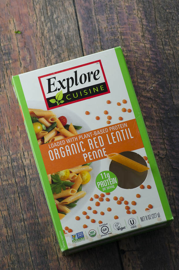 A box of Explre Cuisine Organic Red Lentil Penne on a wooden surface