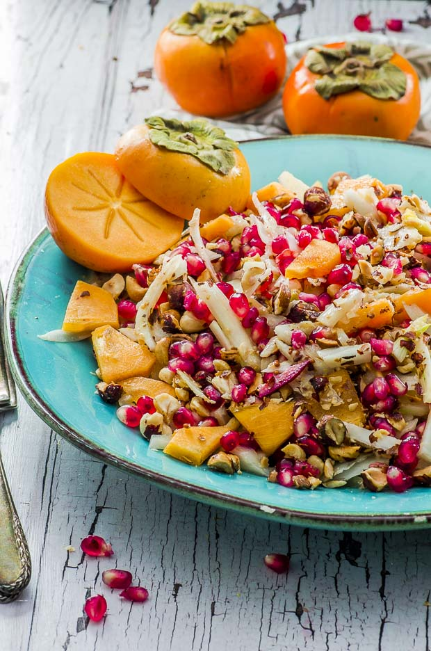 Persimmon Fennel Salad with Pomegranate Seeds and Hazelnuts on a teal serving platter with a persimmon sliced in half on the top left corner and two whole persimmons above the plate, on a white wooden surface.