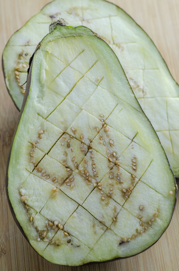 Close up of a raw eggplant sliced in half and scored on a diamond pattern
