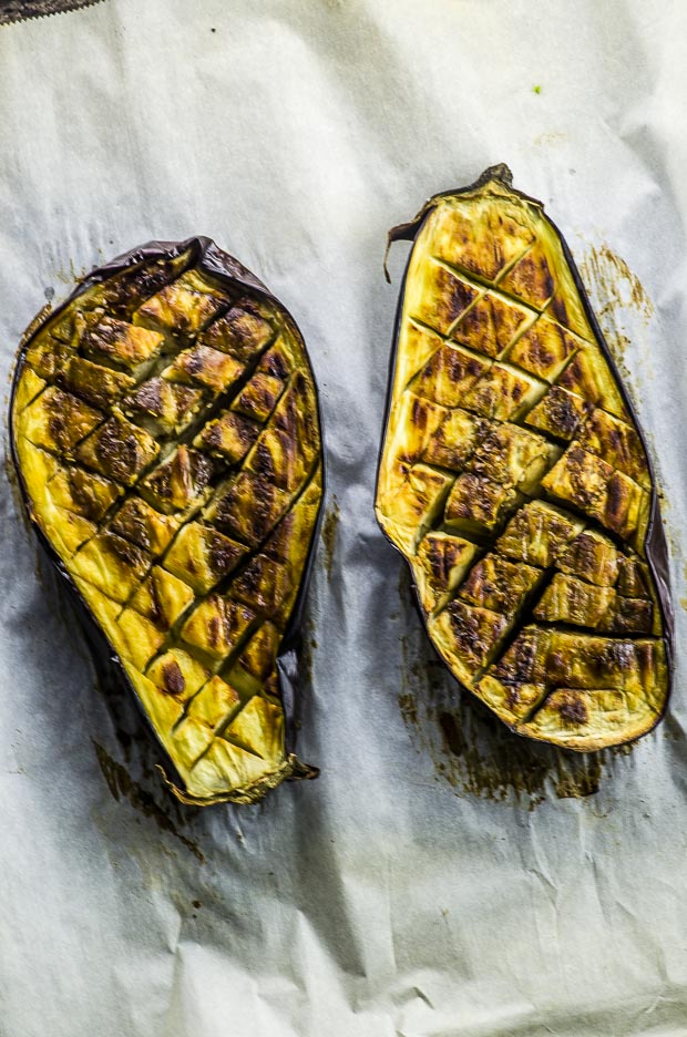 Birds eye view of roasted eggplant sliced in half and scored on a diamond pattern on a piece of parchment paper
