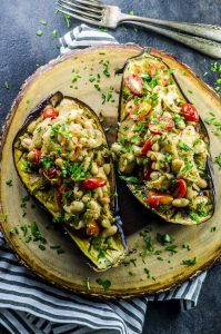 Two eggplant halves baked and filled with cooked fennel, white beans, tomatoes and parsley