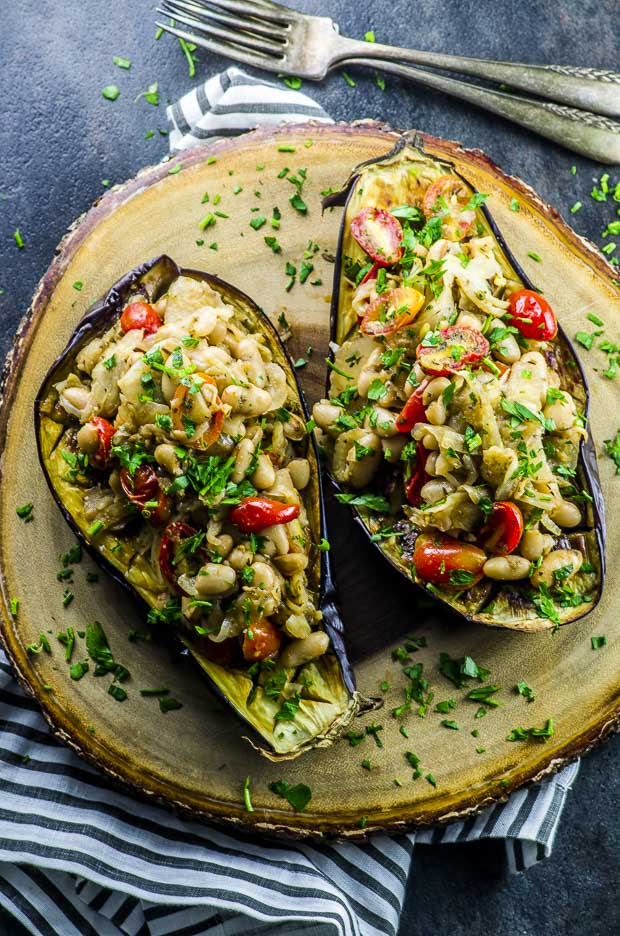 Birds eye view of Stuffed Eggplant with Fennel and White Beans on a round wooden board, over a gray and white cloth napkin on a dark gray surface