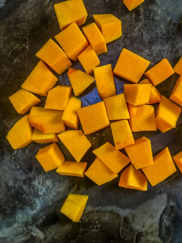 Diced butternut squash on a dark gray surface