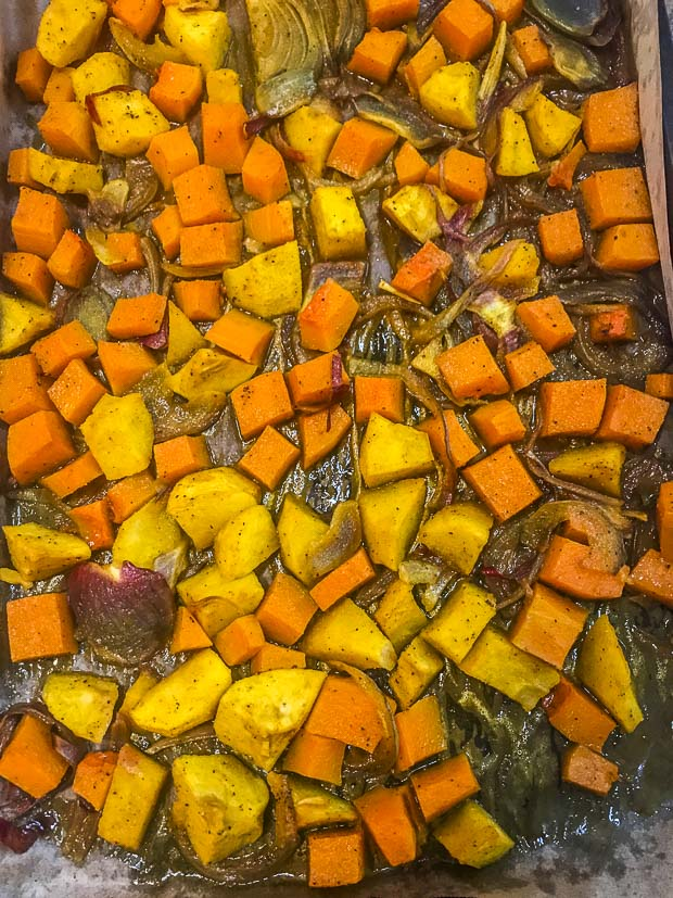 Birds eye view of roasted butternut squash, apples and red onions on a baking sheet
