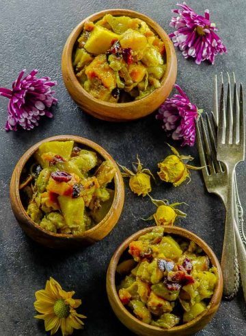 Birds eye view of the vegan butternut squash apple stuffing served in small wood bowls on a dark gray surface, with two forks placed on the right hand side and pink and yellow flowers scattered