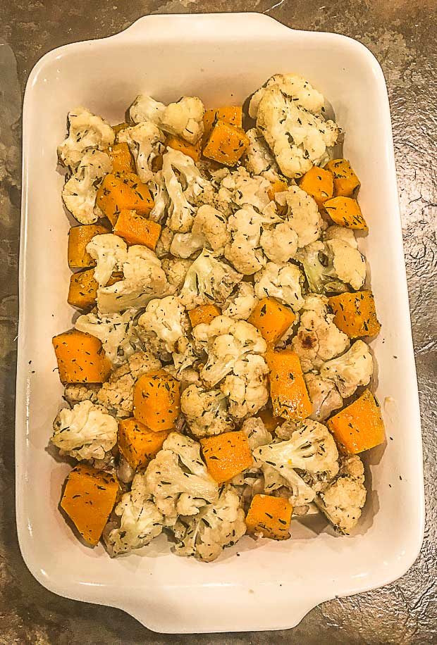 Chopped Butternut squash and cauliflower on a baking dish on top bechamel sauce
