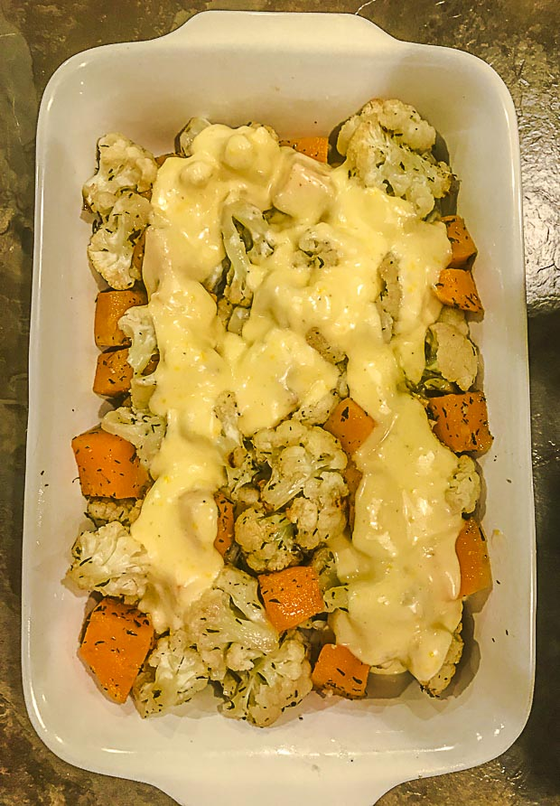 Bechamel sauce spread on top on chopped butternut squash and cauliflower pieces