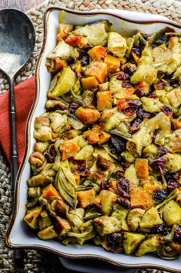 Birds eye view of the vegan butternut squash apple stuffing in a white, gold rimmed baking dish over a red napkin on a woven place mat, with a serving spoon placed on the left hand side