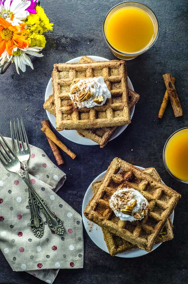 Birds eye view of 2 plates with 2 Vegan Gingerbread Buttermilk Waffles on each plate. the waffles are topped with coconut whipped cream, cinnamon, and pecans. There is a small metal cup with orange and hot pink flowers on the left upper corner of the image. On the bottom left there is a gray napkin with pink polka dots and 2 forks on top. On the right there are 2 clear cups with apple cider and 2 cinnamon sticks on the table top.