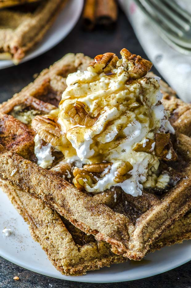 a close up image of 2 Gingerbread Vegan Waffles on a white plate topped with coconut whipped cream, cinnamon, and pecans