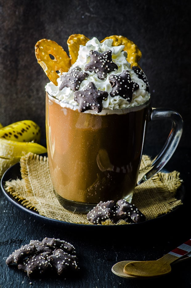 A glass mug of peanut butter and banana vegan hot chocolate topped with coconut whipped cream, three pretzel thins and 5 chocolate coversed star shaped cookies, on a small plate with two woven coasters