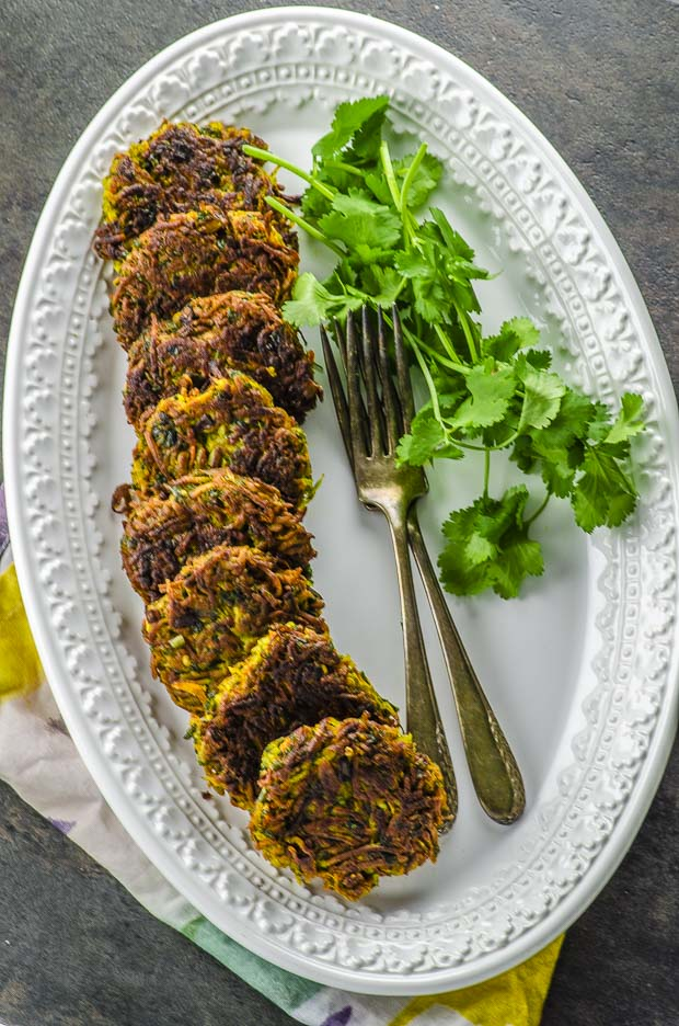 Long oval plate with parsnip and carrot latkes on one side , two forks and a bunch of cilantro on the other side of the plate