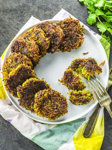 A round plate with carrot and parsnip vegan latkes forming aa semi circle and a half eaten vegan latke on the side with a fork into the latke