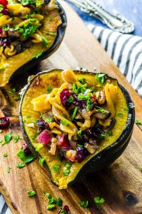Two stuffed butternut squash halves place on a wood board