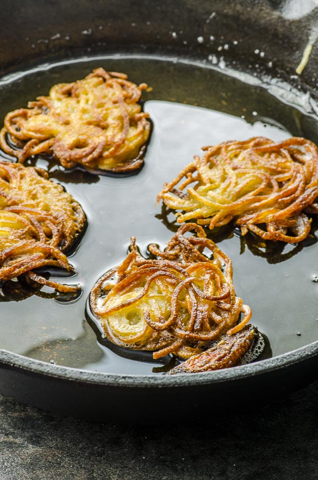 Four potato latkes frying in oil on a cast iron skillet