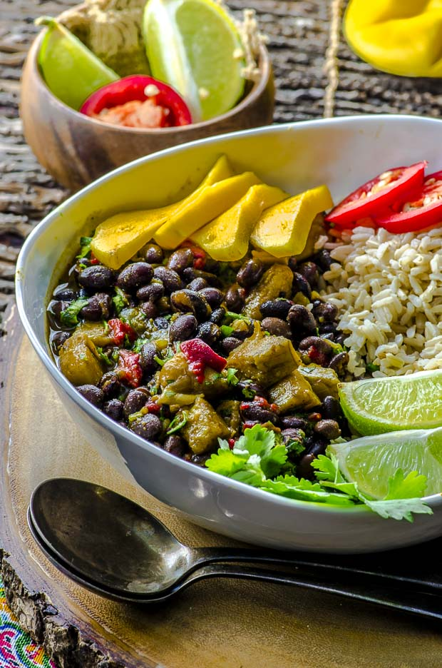 A large white bowl with black beans and rice with plantains, topped with mango slices, two lime slices, hot pepper slices and cilantro on a round wooden board, wit htwo silver spoons on the left side, and a small wooden board with lime wedges and a pepper slice in it