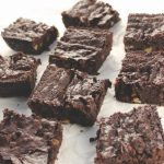 Squares of Fudgy Double Chocolate Brownies on a white parchment paper