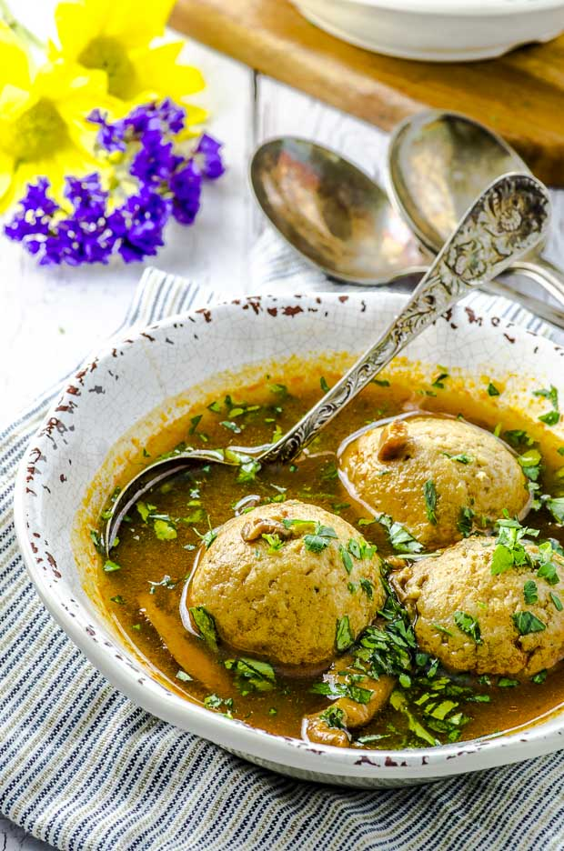 A white bowl of vegetarian matzah ball soup in a deep rich colored golden broth. There is a spoon on the bow and two more spoons on the background with some flowers .