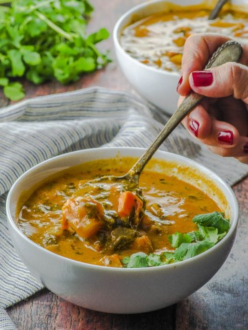 Side view of a bowl of peanut soup with spinach and sweet potatoes. A. hand is shown taking a spoonful of peanut soup from the bowl . in the background there is another white bowl of soup and a bunch of cilantro.