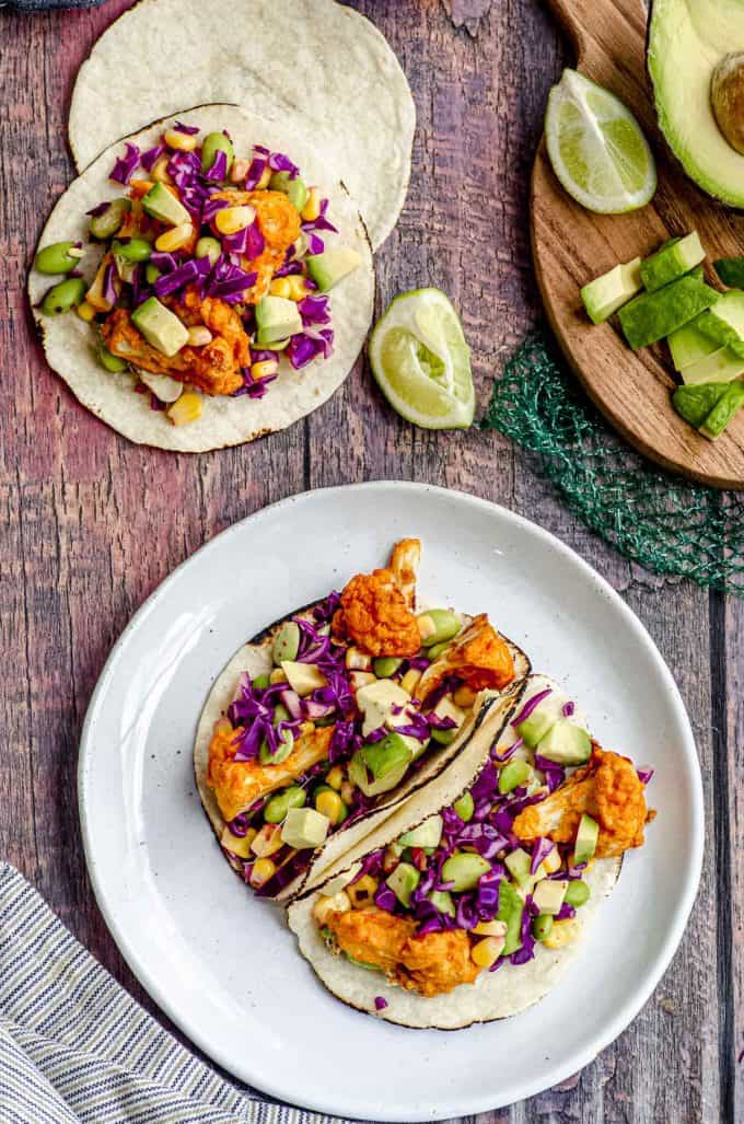 Overhead view of two vegan tacos on a white plate