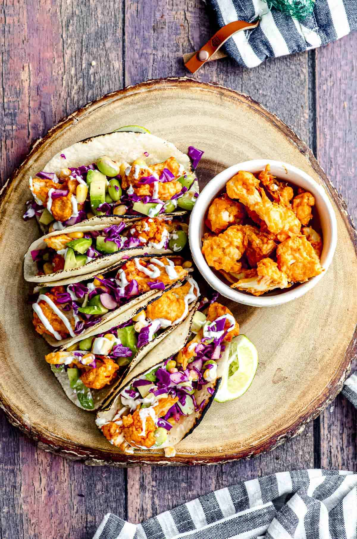 Over head view of a round wood board with buffalo cauliflower tacos