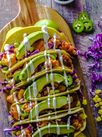 Birds eye view of five buffalo cauliflower tacos with shredded purple cabbage, edamame and corn, topped with avocado slices and cashew cream, on a wooden board. On the right side ther are 3 jalapeno pepper slices, some shredded cabbage and a few corn kernels