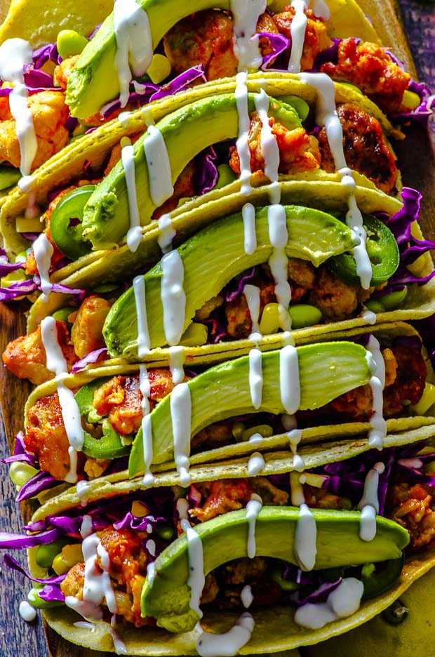 Close up of five buffalo cauliflower tacos with shredded purple cabbage, edamame and corn, topped with avocado slices and cashew cream.