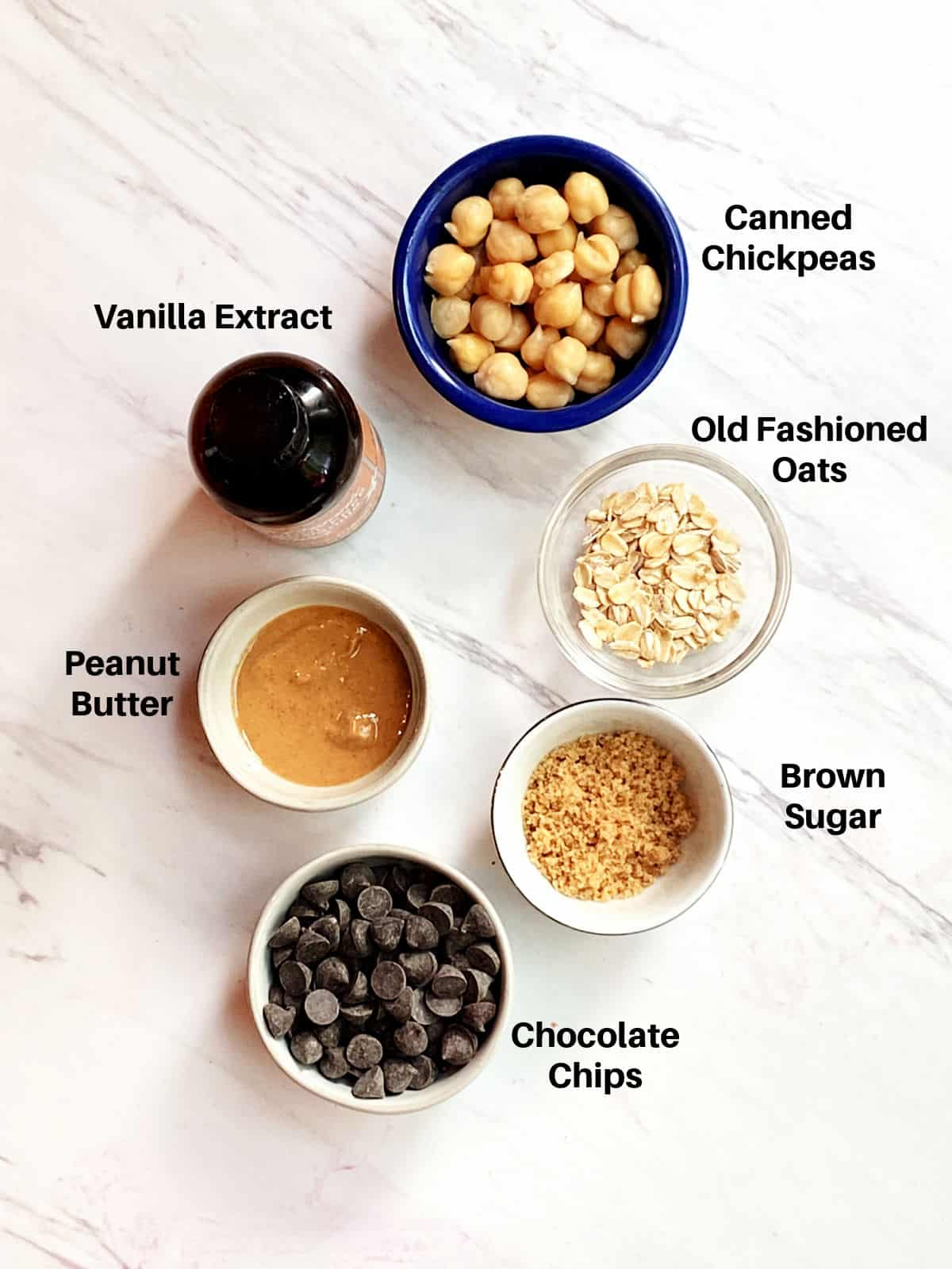 Chickpea cookie dough ingredients labeled.  Chickpeas, oats, peanut butter, vanilla extract, chocolate chips and brown sugar