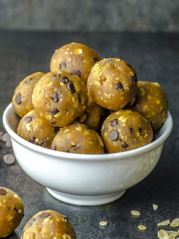 a pile of chocolate chip chickpea cookies dough balls on a white bowl and placed on a black surface