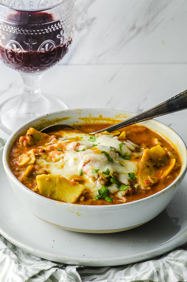 A white bowl with lasagna soup with melted cheese on top and a silver spoon, over a white surface, with a glass of wine in the background