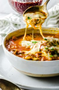 Close up of the lasagna soup with melted cheese on top and a silver spoon scooping it put, in a white bowl over  a white surface