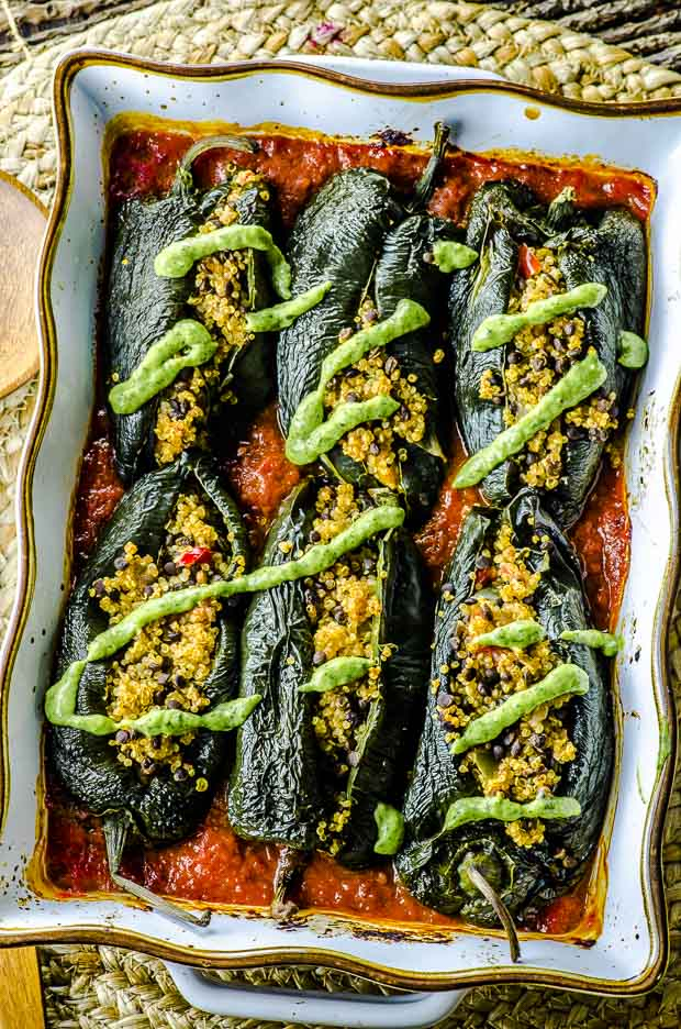 Birds eye view of stuffed poblano peppers with a drizzle of avocado cilantro cream over tomato sauce in a gold rimmed white baking dish