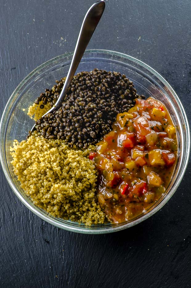 Cooked quinoa, lentils and salsa in a clear glass bowl on a drak gray surface