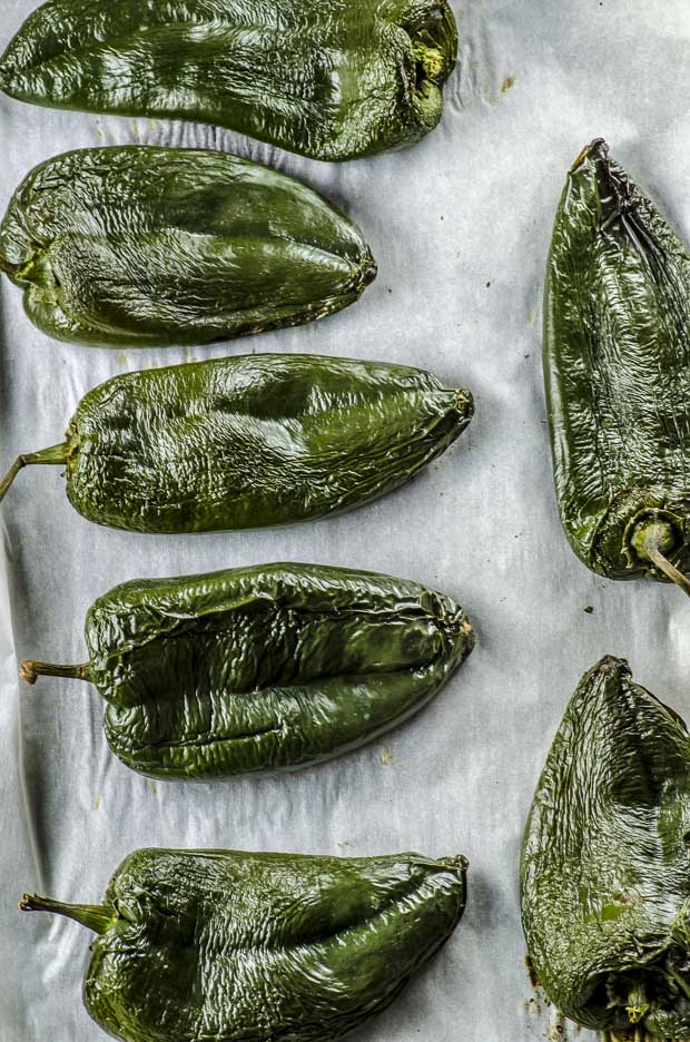 Roasted poblano peppers on a baking sheet lined with parchment paper