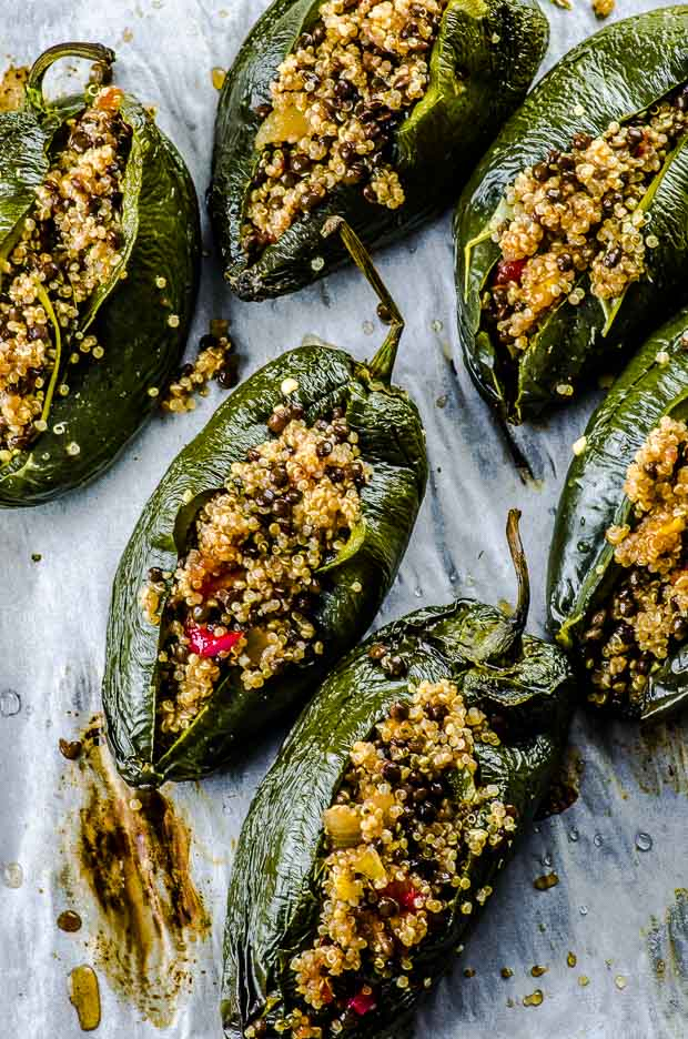 6 poblano peppers stuffed with quinoa, lentil and salsa mixture over parchment paper