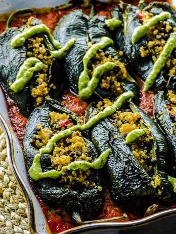 Stuffed poblano peppers with a drizzle of avocado cilantro cream over tomato sauce in a gold rimmed white baking dish