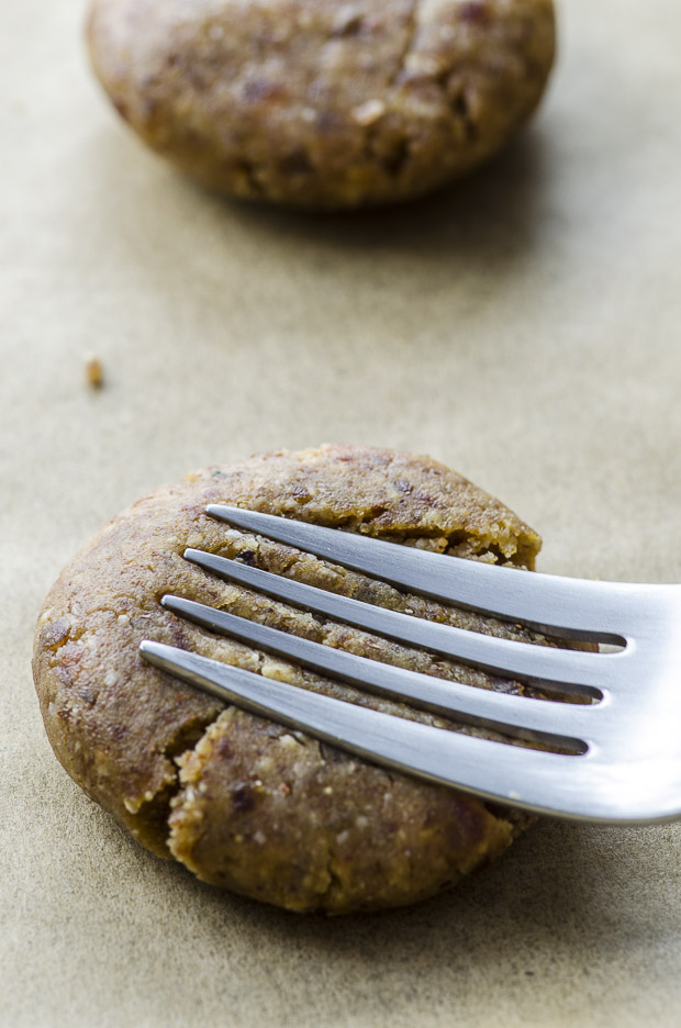 Close up a cookie dough ball with a fork pressing down to make a crisscross patern