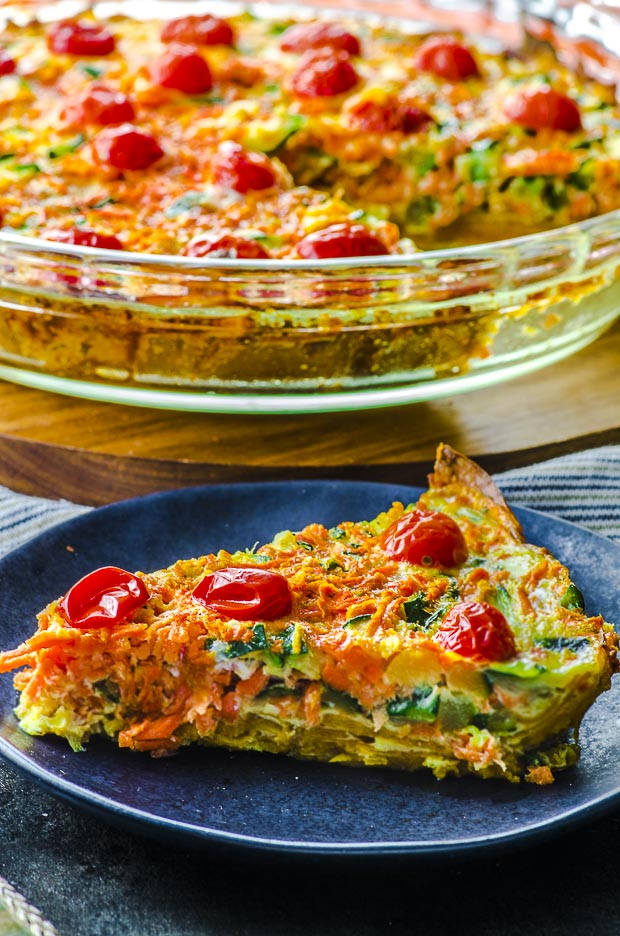 Close up of a slice of quiche with sweet potato crust on a small dark blue plate. In the background there a clear baking dish with the rest of the quiche. A vegetarian passover recipe.
