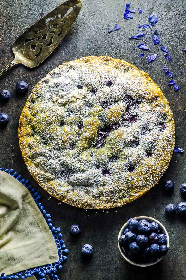 Birds eye view of the lemon blueberry cake, a silver cake cutter, a small bowl of bluerries, a cream color cloth napkin with blue fringes, and some scattered blueberries on a dark gray surface