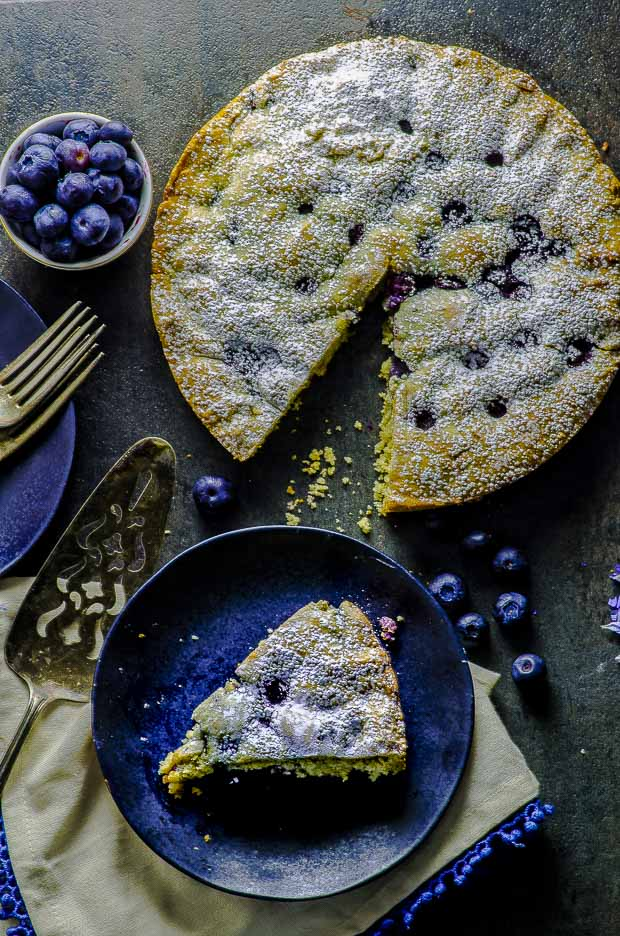 Birds eye view of a slice of the lemon blueberry cake, on a a cream color cloth napkin with blue fringes, a silver cake cutter, a small bowl of bluerries, and some scattered blueberries on a dark gray surface