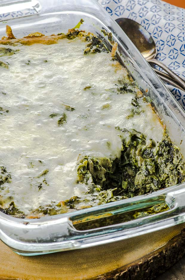 Close up of high protein spinach pasta bake in a rectangular clear baking dish, on a round wooden board on a blue and white patterned cloth napkin