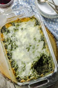 Birds eye view of high protein spinach pasta bake in a rectangular clear baking dish, on a round wooden board on a blue and white patterned cloth napkin