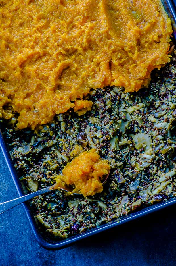 Close up of the sweet potato shepher's pie with the mashed sweet potaotes being spread on top of the filling