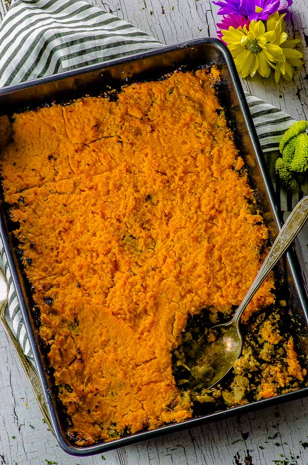 Birds eye view of the Sweet Potato Shepherd's Pie with a silver spoon, on a white an gray striped cloth napkin and a yellow flower on the corner