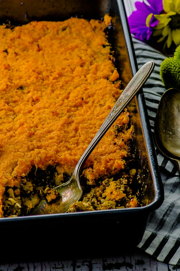 Close up of the Sweet Potato Shepherd's Pie with a silver spoon, on a white an gray striped cloth napkin