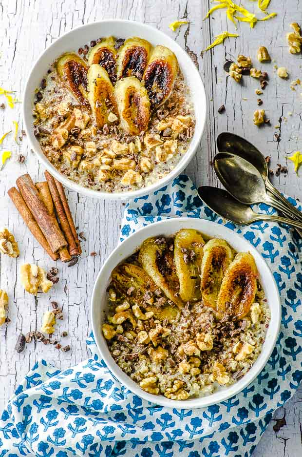bird's eye view of two white bowls of quinoa breakfast topped with caramelized bananas, walnuts, cocoa nibs and a sprinkle of cinnamon. The bottom bowl is placed on a white and blue napkin with a flower print. on the right there are 3 spoons and on the left 3 pieces of cinnamon bark.