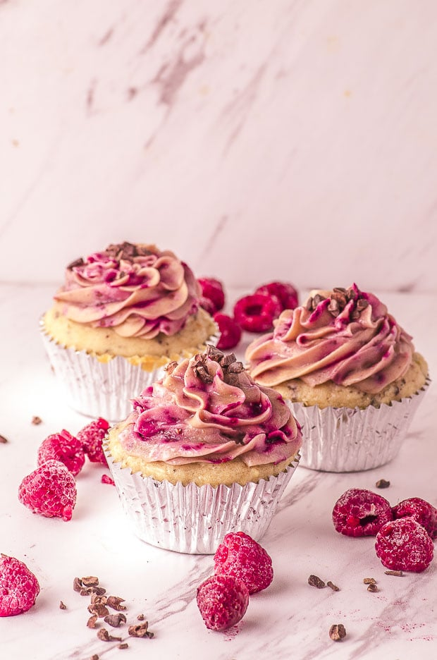 Picture of three raspberry cupcakes, with some raspberries and cacao nibs scattered around