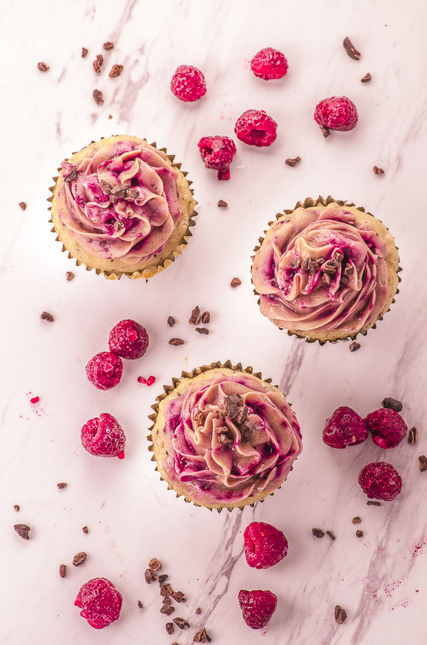 Birds eye view of three raspberry cupcakes, with some raspberries and cacao nibs scattered around